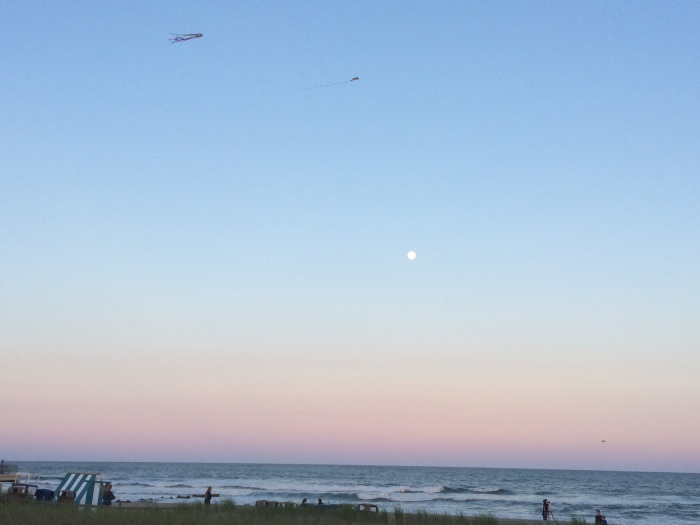 Kites, the moon, and the Atlantic Ocean at sunset at Ocean City, New Jersey, USA.